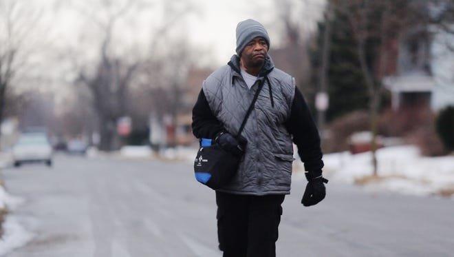 James Robertson, 56, of Detroit, walks toward Woodward Ave. in Detroit to catch his morning bus to Somerset Collection in Troy before walking to his job at Schain Mold & Engineering in Rochester Hills on Thursday, Jan. 29, 2015.