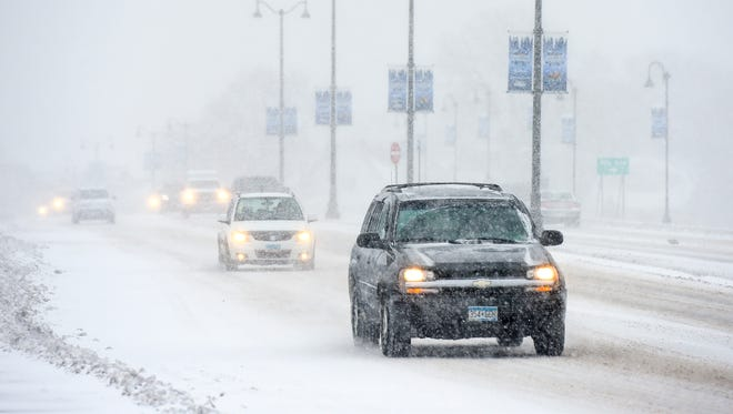 Traffic was slow as heavy snow falls Saturday, April 14, on Minnesota Highway 23 through downtown St. Cloud.
