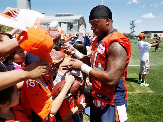 FILE - In this Friday, July 31, 2015, file photo, Denver Broncos linebacker Brandon Marshall signs autographs for fans after the opening session at the team's NFL football training camp in Englewood, Colo. Marshall is among a growing number of elite players in the NFL who started on the teams' practice squad only to graduate to stardom on the first team. (AP Photo/David Zalubowski)