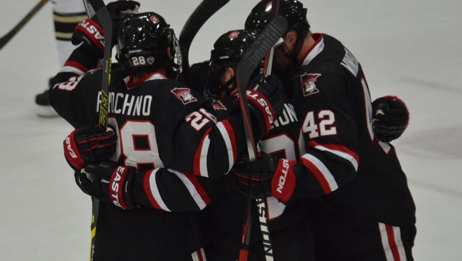 St. Cloud State players celebrate a first-period goal by David Morley on Friday at Logan Ice Arena in Kalamazoo, Mich.