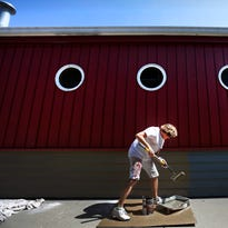 Sue Miller paints the exterior of the former Nauts Landing on April 18, 2015, in Menasha, Wis. The restaurant has new owners and will reopen on May 15, 2015 as Lake House Supper Club. Wm.Glasheen/Post-Crescent Media