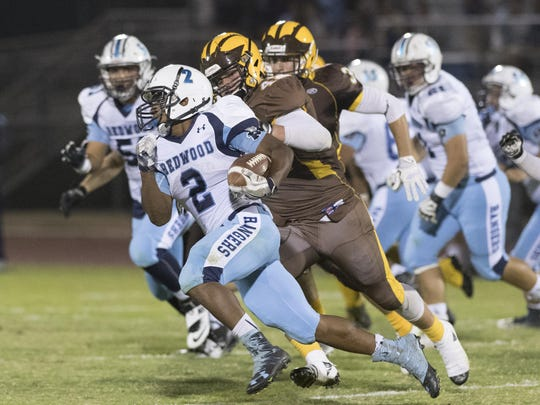 Redwood's Michael Harris carries the football against Golden West on Sept. 30 at Groppetti Automotive Visalia Community Stadium.