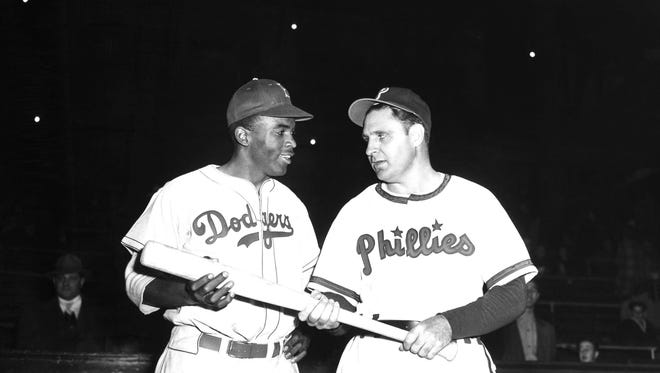 In a May 9, 1947 file photo, Jackie Robinson, left, Brooklyn Dodgers' first baseman, looks over the bat Philadelphia Phillies manager Ben Chapman uses during practice, as he prepared to play his first Philadelphia game for the Dodgers. The Philadelphia City Council unanimously passed a resolution Thursday, March 31, 2016, naming April 15, 2016 as a day to honor Robinson's achievements and to apologize for the racism he faced while visiting Philadelphia in 1947. Robinson was refused service by a local hotel and then taunted by Philadelphia Phillies manager Ben Chapman, who, along with players, mercilessly hurled racial slurs at Robinson each time he came to bat. (AP Photo, File)