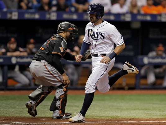 Tampa Bay Rays' Curt Casali, right, races home in front of Baltimore Orioles catcher Welington Castillo on a sacrifice fly by Peter Bourjos during the fourth inning of a baseball game Friday, Sept. 29, 2017, in St. Petersburg, Fla. (AP Photo/Chris O'Meara)