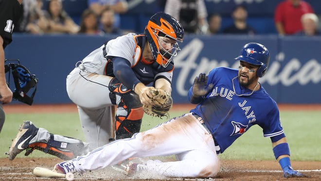 Devon Travis is tagged out at home plate by Grayson Greiner in the eighth inning at Rogers Centre on Saturday.