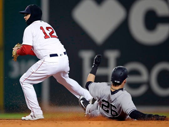 New York Yankees' Tyler Austin, right, makes contact with Boston Red Sox second baseman Brock Holt as he slides into second during the third inning of a baseball game at Fenway Park in Boston, Wednesday, April 11, 2018. Austin was called out due to slide interference.