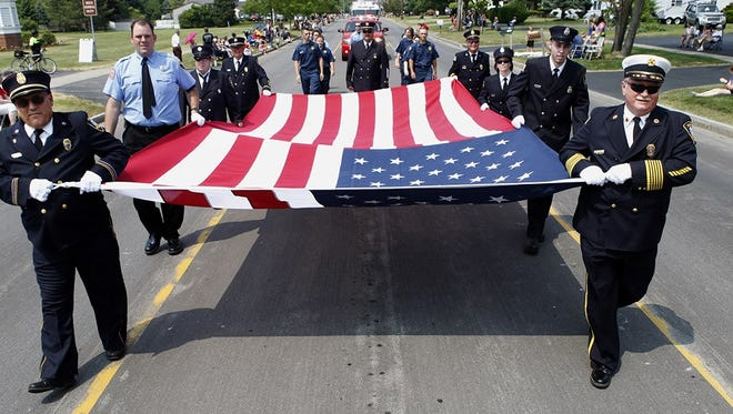 The National 9/11 Flag stopped in Webster in July during the Webster Firemen's Carnival. Firefighters and the public had a chance to hold a section of the flag as patriotic songs were played.