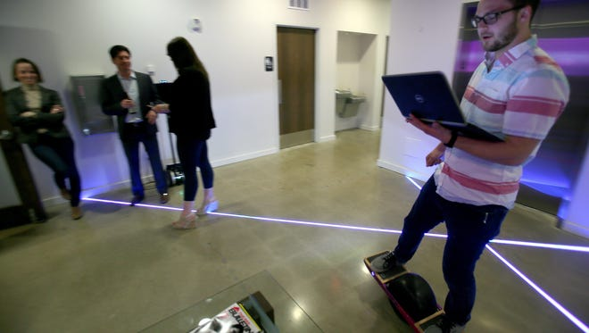 """Zak Sarakun, 22 of Clinton Township, uses a """"One Wheel"""" to move around the large offices of Vectorform, a tech and invention company in Royal Oak on Wednesday, April 19, 2017."""