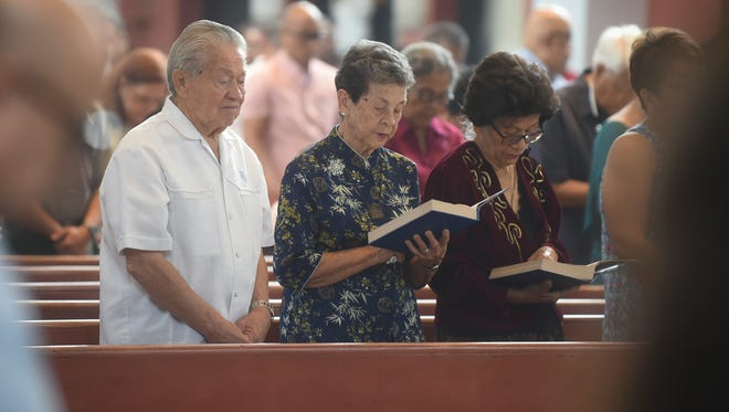 Parishoners follow along with a reading during a Mass in honor of Guam's World War II survivors at the Dulce Nombre de Maria Cathedral-Basilica in Hagåtña on Dec. 8, 2016.
