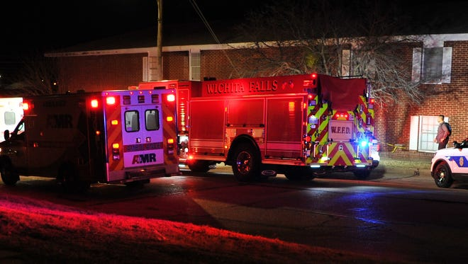 First responders and emergency medical personnel treat two gunshot victims Monday night outside the Plantation Apartments, 1201 Austin St.