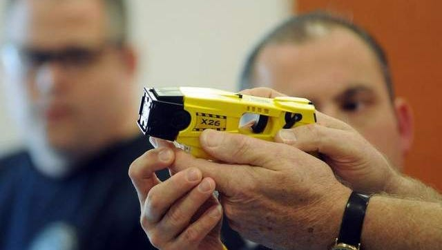 In this file photo from December 2011, a City of Poughkeepsie police officer is shown how to properly use a Taser stun device during a training session.