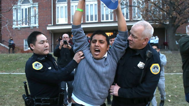 Self-identified undocumented immigrant Marco Malagon, of Dallas, is escorted off the grounds of Hoyt-Sherman Place after a disruption during Texas Gov. Rick Perry's speech during the Iowa Freedom Summit on Saturday.