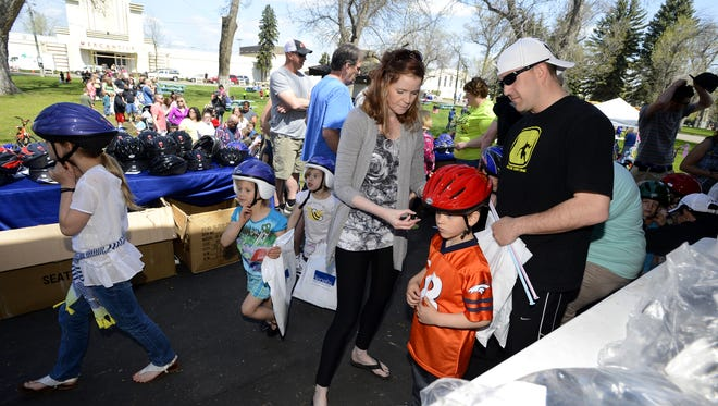 Karen Ogden helps fit Ben Cunningham, age 5, with a bike helmet during a previous Safety First Rally hosted by Benefis Health System.