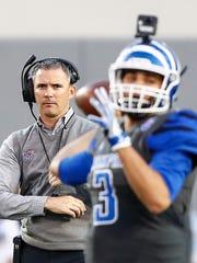 Memphis head coach Mike Norvell (left) looks as quarterback