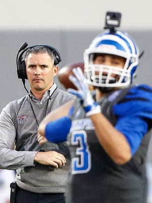 Memphis head coach Mike Norvell (left) looks as quarterback Brady White (right) makes a pass during their spring football game at Liberty Bowl Memorial Stadium.