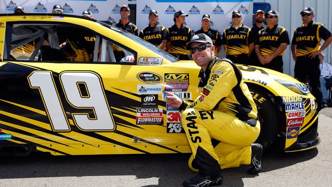 Carl Edwards, driver of the #19 Stanley Toyota, places the Coors Light Pole Award decal after qualifying for the NASCAR Sprint Cup Series Cheez-It 355 at Watkins Glen International on August 6, 2016 in Watkins Glen.