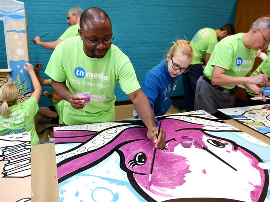 Tennessean reporter Getahn Ward, left, and Olivia Cass, daughter of TN Media Marketing Manager Heather Cass, paint an octopus for a children's mural during Make A Difference Day on Saturday, Oct. 24, 2015, in the Thompson Lane branch library in Nashville.