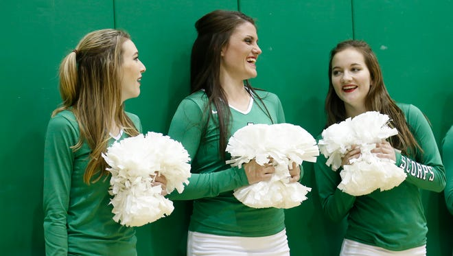 From left, Emily Bliss, Taylor Crum and Breckan Campbell chat on Thursday as they cheer on Farmington High School's boys basketball team during the Marv Sanders Invite at Scorpion Gym in Farmington.