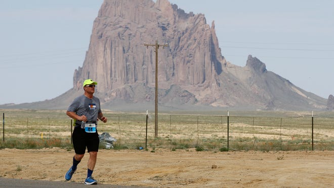 Greg Capra runs along Indian Service Route 13 during the 2015 Shiprock Marathon.