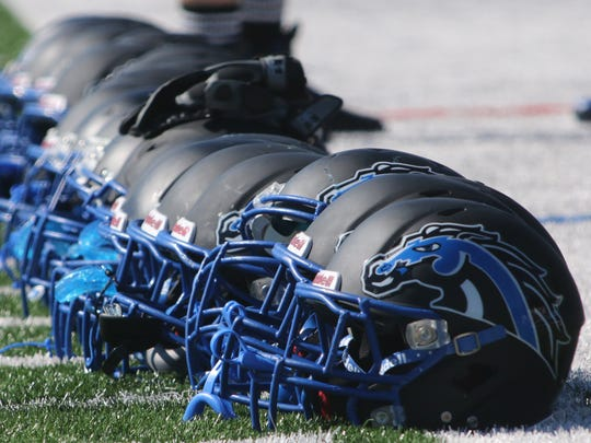 Helmets are lined up on the football field at Millbrook High School during a preseason practice on Aug. 22.
