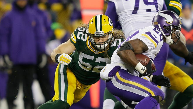 Green Bay Packers inside linebacker Clay Matthews (52) tackles Minnesota Vikings running back Adrian Peterson (28) in the backfield at Lambeau Field.