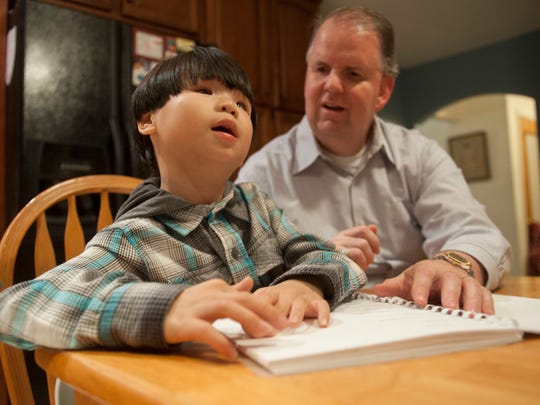 Michael Corman, a blind attorney who is fluent in Braille, sits next to his 7-year-old visually impaired son Jon Paul as he reads Braille in their Barrington home. Jon Paul, who has only one eye and significantly limited vision, is learning how to read and write using Braille.