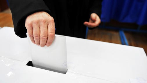 A stock image of a person voting.