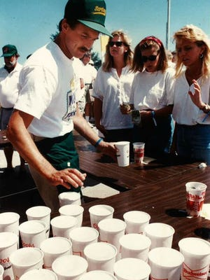 Scott Runyon serves beer while working at a stand at the Arkansas State vs. CSU football game at Hughes Stadium on Aug. 31, 1991.