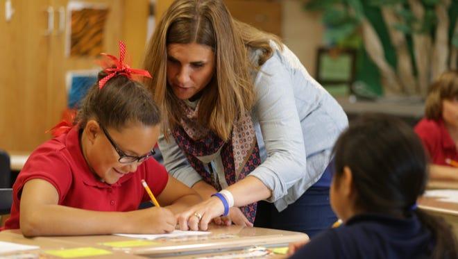 Julie Beaty, a teacher at Indianapolis Public Schools' Eleanor Skillen School 34, on May 13, 2015, assists students Gabi Sellers (left) and Nashley Ruiz.