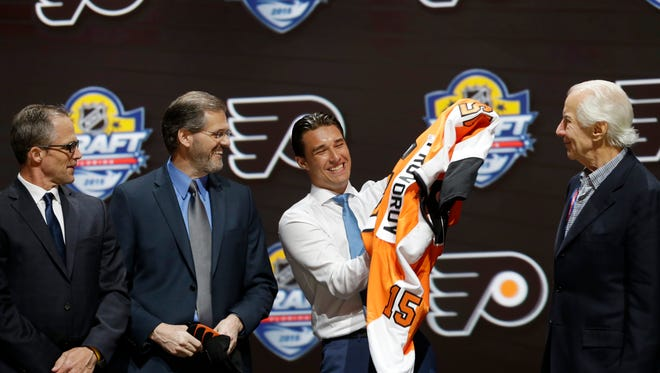 Ivan Provorov, second from right, of Russia, puts on a Philadelphia Flyers sweater after being chosen seventh overall during the first round of the NHL hockey draft, Friday, June 26, 2015 in Sunrise, Fla. (AP Photo/Alan Diaz)