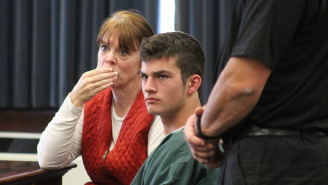 Great Falls High School student Brock Doty, center, and his mother, Carrie Doty Sammons, react as criminal charges are read against him in District Court on Friday.