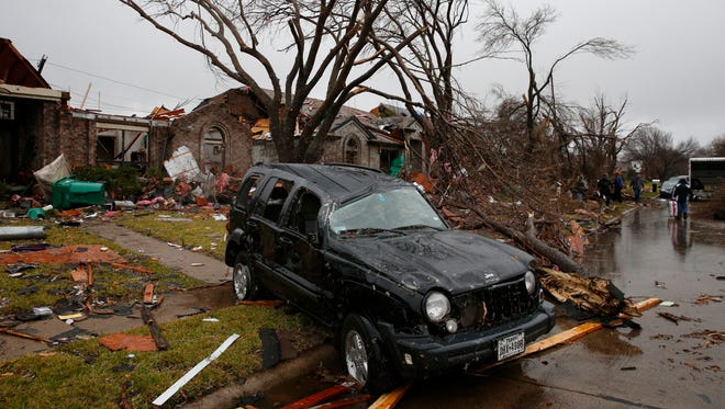 A Jeep Liberty sits destroyed on Shipman Street after Saturday's tornado in Rowlett, Texas on Sunday. Tornadoes that swept through the Dallas area caused substantial damage and at least 11 people died either from the storm or related traffic accidents and dozens of people were injured.