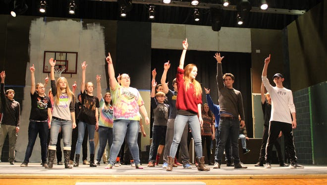 Newfield High School junior Devonn McKenna, center in red shirt, practices with the cast of High School Musical