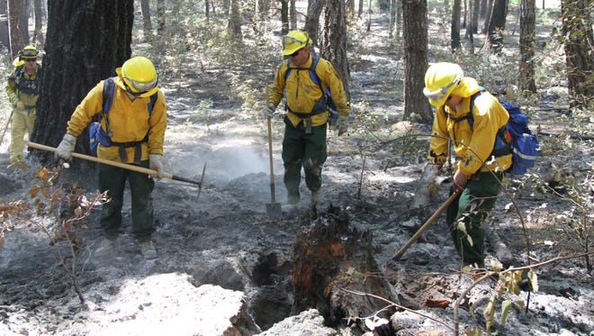 FILE: A firefighting crew from Task Force Alpha, California Army National Guard, clears a hot spot during mop up duties Aug. 9 near the mountains of Wildcat Butte.