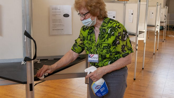 Election worker Cheryl Pecor cleans the voting booths after every voter in the Southbridge polling place during the town election Tuesday.