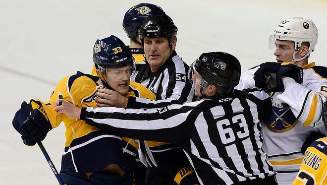 Linesmen Greg Devorski (54) and Trent Knorr (63) restrain Nashville Predators forward Colin Wilson (33) from fighting with Buffalo Sabres defenseman Rasmus Ristolainen (55) in the third period. Ristolainen had been recalled from the Rochester Americans for Thursday's games.
