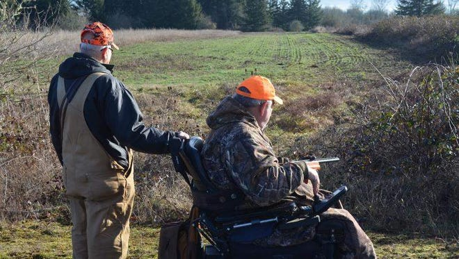 Jerry Ray of the Mary's Peak Hound Club and Darrel Von, an associate member of the Oregon Chapter, Paralyzed Veterans of America, wait for Ray's dogs to flush a rabbit during the 24th annual rabbit hunt for the disabled sponsored by the hound club