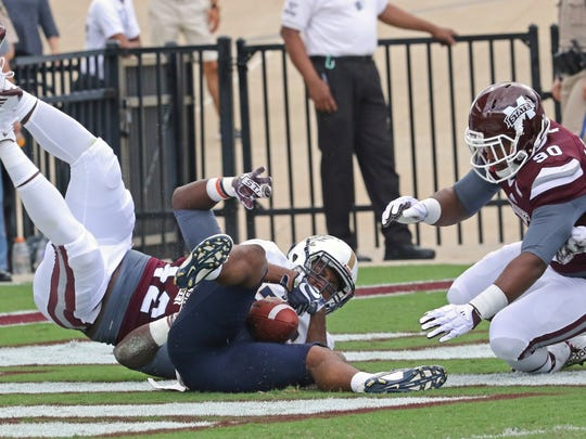 Mississippi State defensive lineman Marquiss Spencer (42) is upended and downs Charleston Southern running back Chanin Hamilton (25) in the end zone for a safety as Mississippi State defensive back Chris Stamps (30) assists during the first half of an NCAA college football game in Starkville, Miss., Saturday, Sept. 2, 2017.