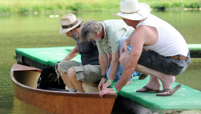 Sebastian Blanchard, front, and Doc Patterson help Cary Hudson into a pirogue at the start of the inaugural Piney Woods Picnic at Pep's Point Water Park.