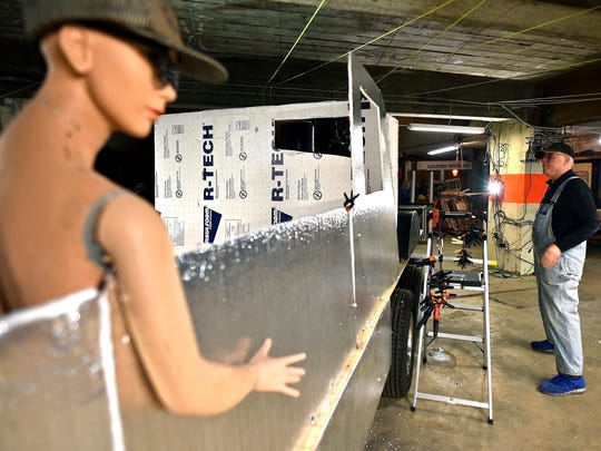 A mannequin stands in as a mock passenger as Jeff Daly works on his latest project in his studio.