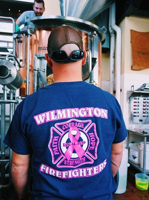 Wilmington firefighter Stephen Facciolo helps brew Iron Hill's Last Alarm IPA in October.