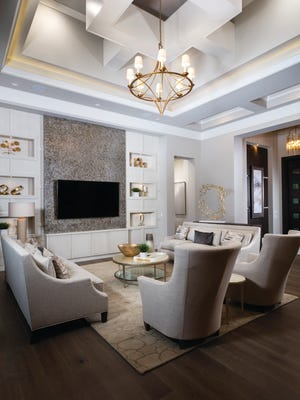 The great room of the St. Martin II by Florida Lifestyle Homes features a tray ceiling with suspended beams.