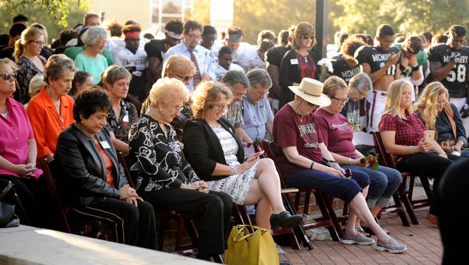 McMurry University students, alumni and faculty members and their families bow their heads for a prayer Tuesday during the inaugural Ala Cumba ceremony on the school's quad. The ceremony honored alumni and staff who have passed away.