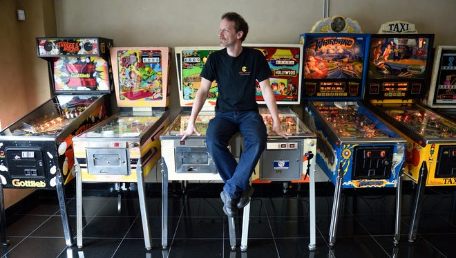 William Smith, owner of Billy's Midway Arcade in Hawthorne, perched atop vintage pinball machines that are available to play at the arcade.