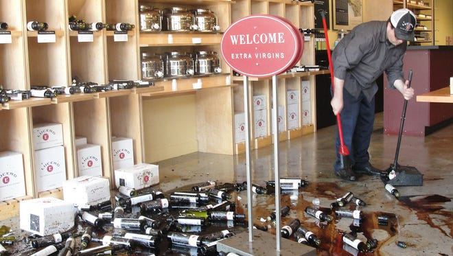 Lucero Olive Oil shop manager David Gadlin sweeps broken bottles of balsamic vinegar and olive oil that crashed to the floor of his shop in downtown Napa, Calif., on Aug. 24. California's governor declared a state of emergency Sunday after a magnitude-6.0 earthquake.