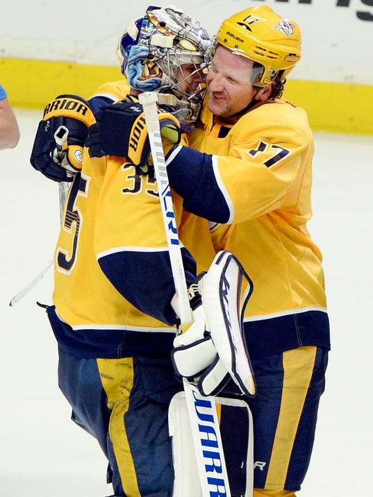 Nashville Predators goaltender Pekka Rinne (35), of Finland, celebrates with left wing Scott Hartnell (17) after the Predators defeated the Minnesota Wild in a shootout in an NHL hockey game Tuesday, March 27, 2018, in Nashville, Tenn. The Predators won 2-1. (AP Photo/Mark Zaleski)