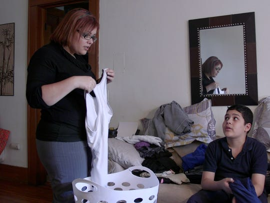 Melody Flores talks with her son, Giovanni Torres, after school as they fold clothes together in their apartment.