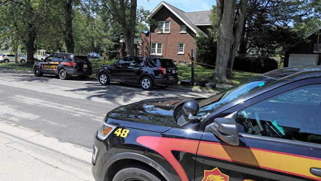 A Sheboygan County Sheriff squad is parked in front a residence North 10th Street Sunday July 30, 2017 in Oostburg, Wis., where an alleged shooting left two men dead.