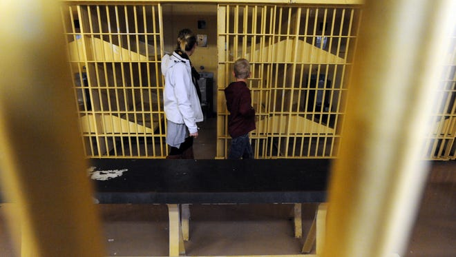 Cassie Strickler, left, and her son Reid Strickler, 7, both from Amanda, look at empty cells in the old Main Street Jail Tuesday, Oct. 31, 2017, in downtown Lancaster. The jail was opened up for a couple of hours Tuesday night for tours.