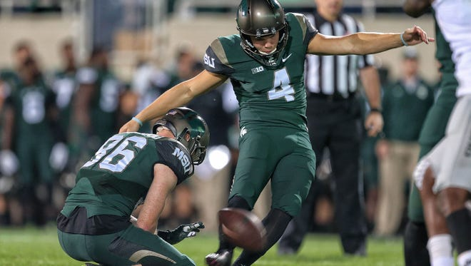 Michigan State Spartans place kicker Michael Geiger (4) kicks a field goal out of the hold of Michigan State Spartans wide receiver Matt Macksood (86) during the 2nd half of a game at Spartan Stadium.